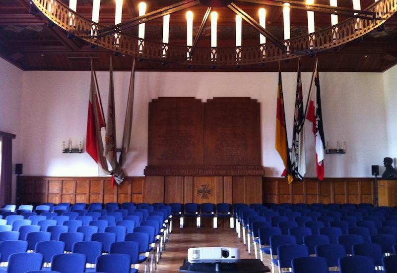 Die Nordwand der Marineschul-Aula vor der Umgestaltung 2016 mit Flaggen deutscher Kriegsschiffe bis 1933. (Quelle: MSM/WGAZ)