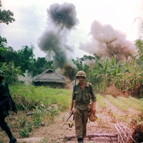 Ein US-Marine im Vietnamkrieg 1966. Im Hintergrund ist die Sprengung einer Vietcong-Stellung zu sehen. (Quelle: wikimedia commons/NARA)