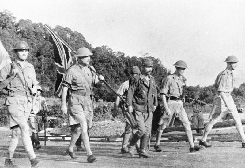Lieutenant-General Arthur Percival (2. v. links mit Union Jack) und seine Offiziere schreiten zur Unterzeichnung der Kapitulation Singapurs am 15. Februar 1942.Quelle: Imperial War Museum (public domain).