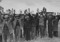 Polish and Jewish inhabitants of Aleksandrow Kujawski hold their arms in the air after their arrest by German soldiers during the conquest of Poland. (© United States Holocaust Memorial Museum, courtesy of Harry Lore)